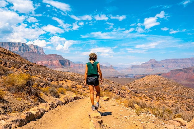 A young woman with green shirt resting on the south kaibab trailhead trekking. grand canyon Premium Photo