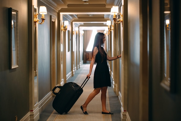 Young woman with handbag and suitcase in an elegant suit walks the hotel corridor to her room. Premium Photo