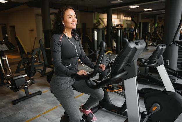 ジムやフィットネスセンターでエアロバイクの練習をしているヘッドフォンを持つ若い女性。ジムの若いスポーティな女性はスマートフォンから音楽を聴きます。有酸素運動をしている女性。 Premium写真