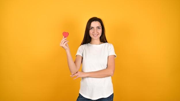 Молодая женщина с сердцем в руках на желтом Premium Фотографии