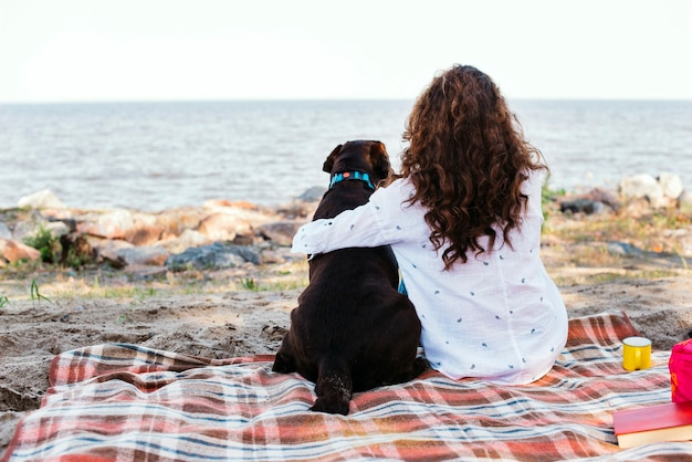 Young woman with her dog at the beach Free Photo