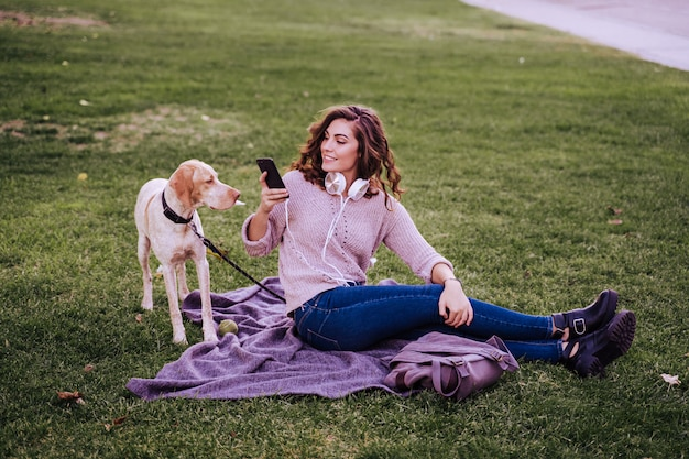 Young woman with her dog at the park. woman using mobile phone Premium Photo