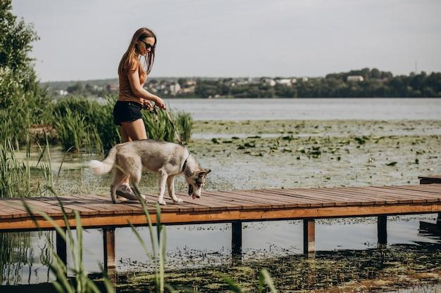 Молодая женщина с ее хаски на берегу озера Бесплатные Фотографии
