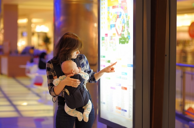 Young woman with her little baby in a shopping mall Premium Photo