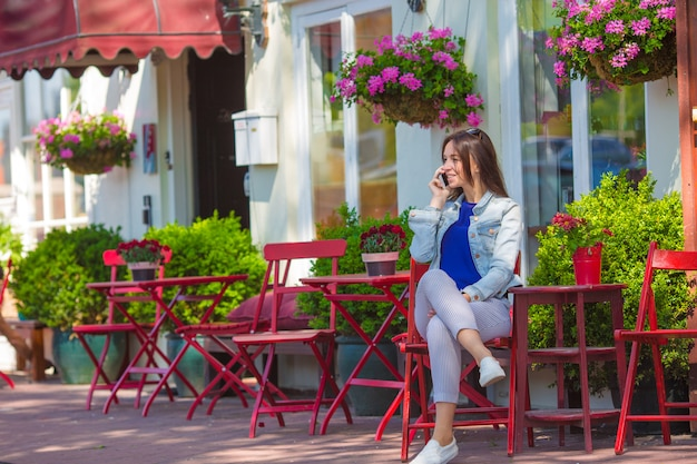 Young woman with her phone at outdoor cafe in european city Premium Photo