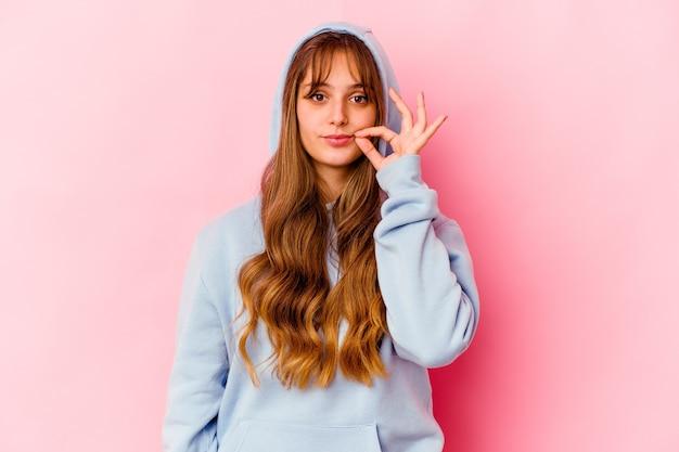 비밀을 유지하는 입술에 손가락으로 노란색 벽에 고립 된 후드와 젊은 여자 프리미엄 사진