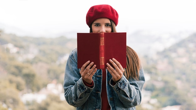 Young woman with knit hat over her head holding book in front of her mouth Free Photo
