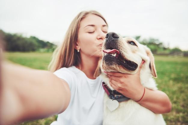 래브라도 야외에서 젊은 여자. 강아지 래브라도 리트리버와 푸른 잔디에 여자. 무료 사진
