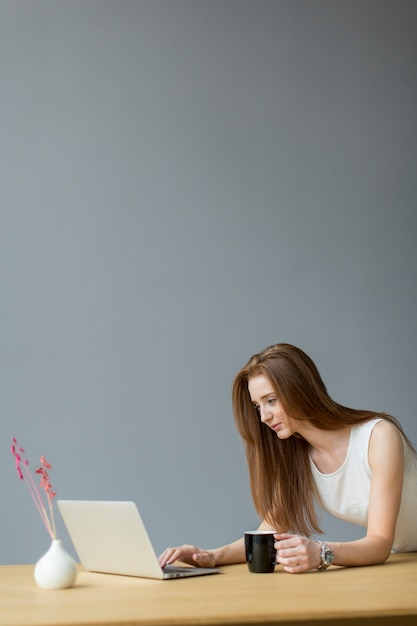 Young woman with laptop in the office Premium Photo