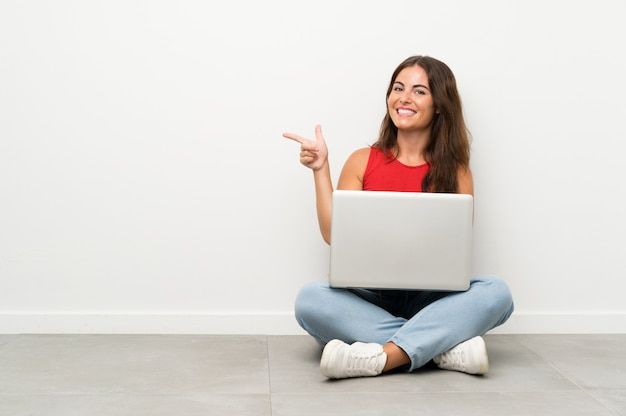 Young woman with a laptop sitting on the floor pointing finger to the side Premium Photo