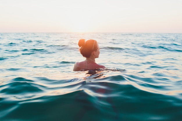Young woman with long hair, blonde, topless, sitting in the water and holding in his hand a bikini top in the sunshine. Premium Photo