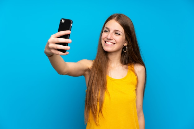 Young woman with long hair over isolated blue wall making a selfie Premium Photo