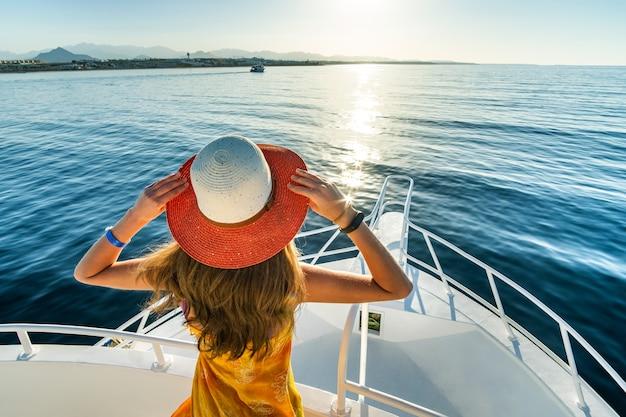 青い海の景色を楽しみながらヨットのデッキに立っている長い髪の若い女性 Premium写真