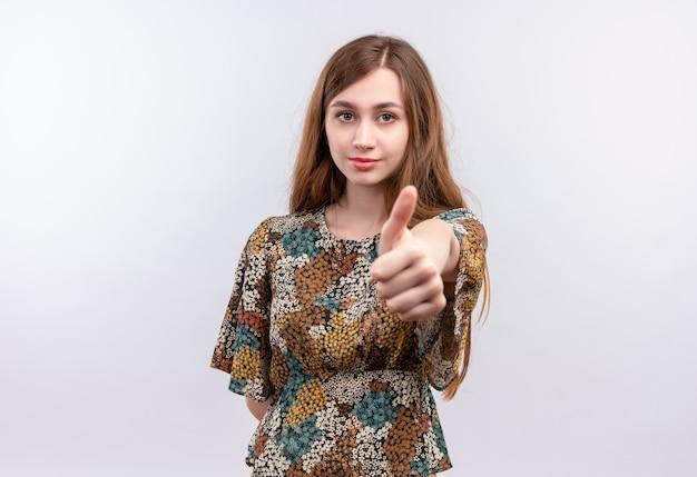 白い壁の上に立って親指を見せて自信を持って笑顔のカラフルなドレスを着て長い髪の若い女性 無料写真