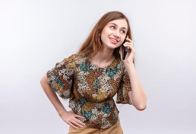 白い壁の上に立っている携帯電話で話しながら笑顔のカラフルなドレスを着て長い髪の若い女性 無料写真