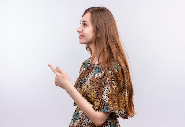 白い壁の上に立っている側に指で横向きに立っているカラフルなドレスを着て長い髪の若い女性 無料写真