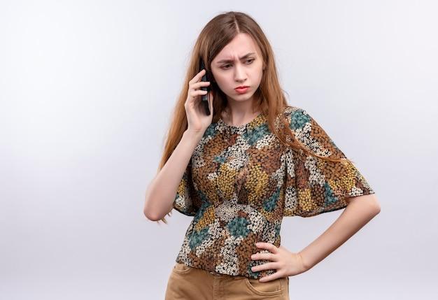 白い壁に立っている眉をひそめている顔と携帯電話で話しているカラフルなドレスを着て長い髪の若い女性 無料写真