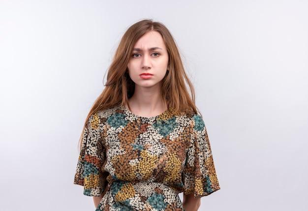 白い壁の上に立っている顔に悲しい表情で非常に見ているカラフルなドレスを着て長い髪の若い女性 無料写真