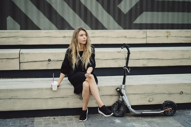 Young woman with long hairs on electric scooter. the girl on the electric scooter drinks coffee. Free Photo