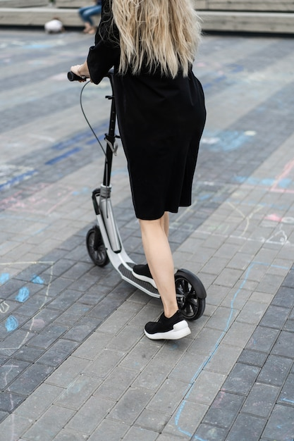 Young woman with long hairs on electric scooter. the girl on the electric scooter. Free Photo