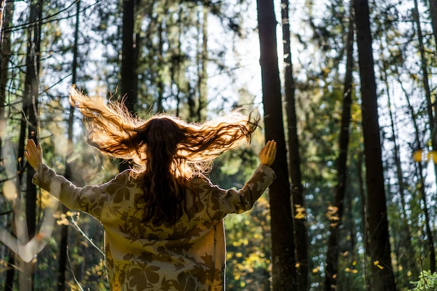 Young woman with long red hair in a linen dress gathering mushrooms in the forest Free Photo
