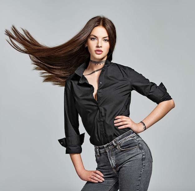 긴 스트레이트 머리-스튜디오에서 젊은 여자. 매력적인 갈색 머리 여자의 초상화입니다. 패션 모델은 검은 색 셔츠와 청바지를 입는다. 섹시한 여성 모델 무료 사진