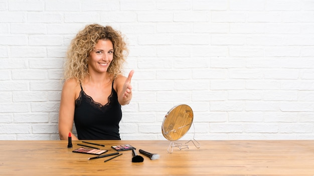 Young woman with lots of makeup brush in a table handshaking after good deal Premium Photo