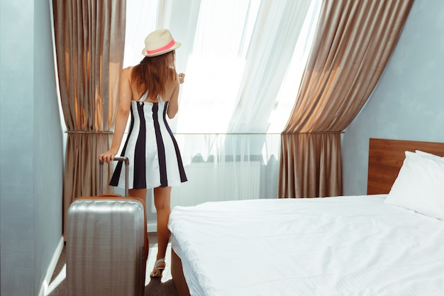 Young woman with luggage in hotel room Premium Photo