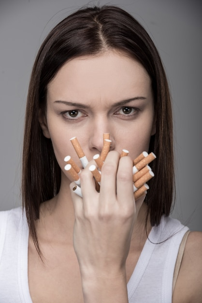 Young woman with many cigarettes in her mouth. Premium Photo