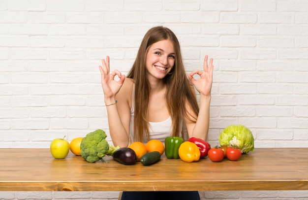 Young woman with many vegetables showing an ok sign with fingers Premium Photo