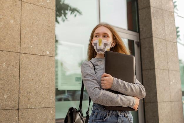 Giovane donna con mascherina medica che tiene il suo computer portatile all'esterno Foto Gratuite
