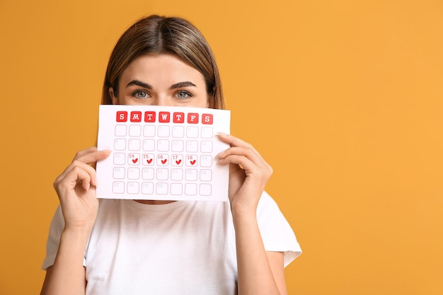 Young woman with menstrual calendar on color surface Premium Photo