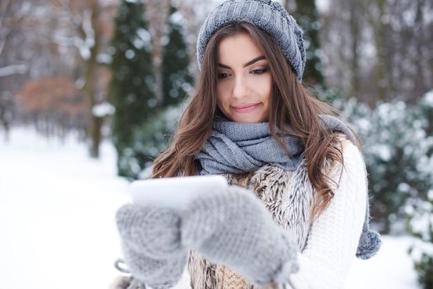 冬の携帯電話を持つ若い女性 無料写真