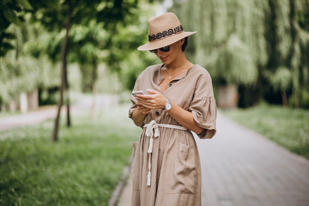 Young woman with mobile phone in park Free Photo