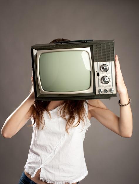 古いレトロなテレビを持つ若い女性 Premium写真