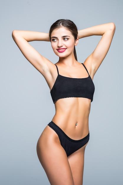 Молодая женщина с идеальным телом носить в черном белье на белой стене Бесплатные Фотографии
