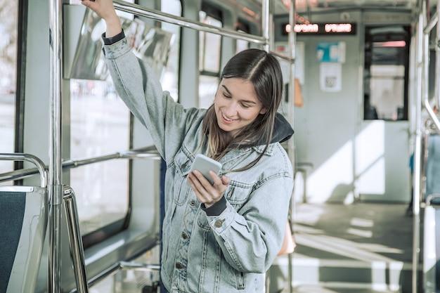 公共交通機関で電話を持つ若い女性。 無料写真