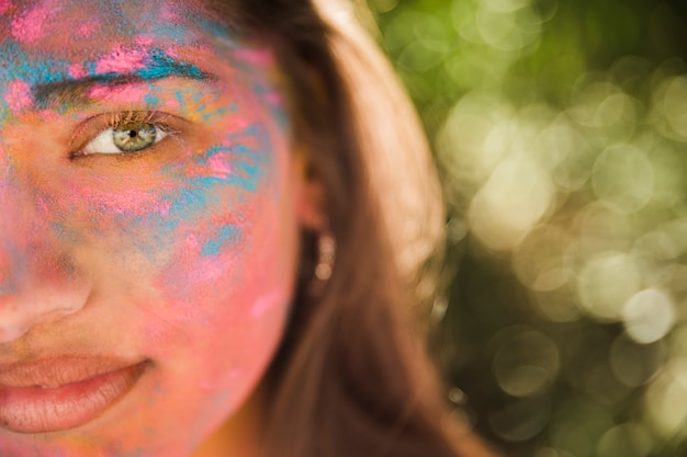 Young woman with pink and blue holi color on her face Free Photo