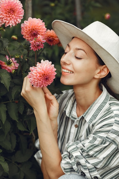 Young woman with pink flowers. lady in a hat. girl in a garden. Free Photo