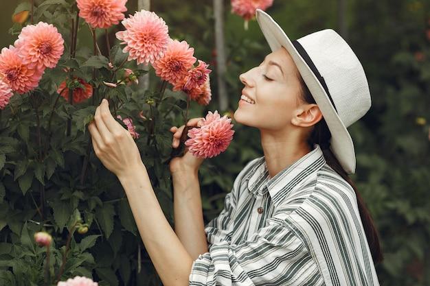 Молодая женщина с розовыми цветами. дама в шляпе. девушка в саду. Бесплатные Фотографии