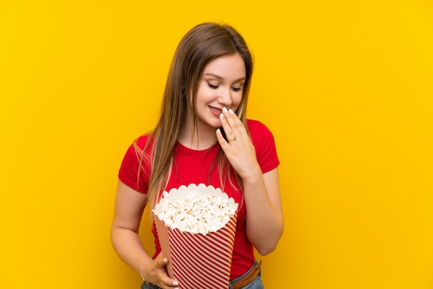 Young woman with popcorns over pink wall smiling a lot Premium Photo