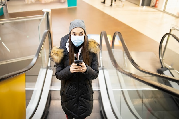Young woman with a protective mask taking the stairs on an airport Premium Photo