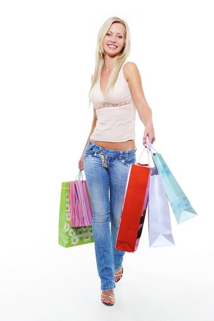 Молодая женщина с покупками гуляет после покупок Бесплатные Фотографии