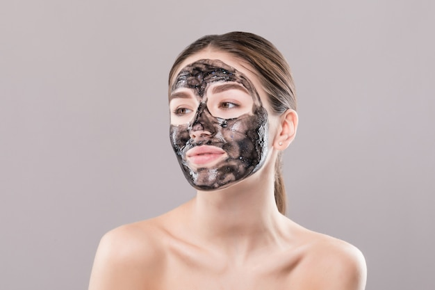 Young woman with purifying black mask on her face isolated on white wall Free Photo