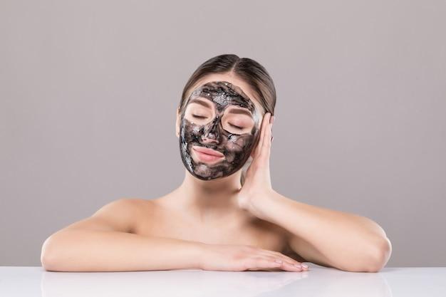 Бесплатно Фото   Молодая женщина с очищающей черной маской на лице,  изолированная на белой стене