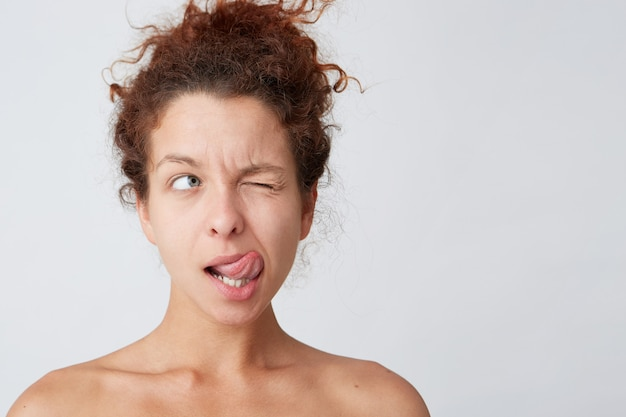Young woman with red curly hair posing and making grimace Free Photo