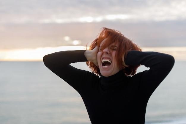 Молодая женщина с рыжими волосами схватившись за голову и громко кричать от душевной боли на фоне моря и заката Premium Фотографии