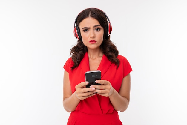A young woman with red lips, bright makeup, dark wavy long hair, in a red suit, black glasses with transparent glasses stands and listens to music in headphones, holds the phone in his hands Premium Photo