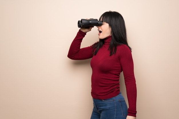 Young woman with red turtleneck and looking in the distance with binoculars Premium Photo