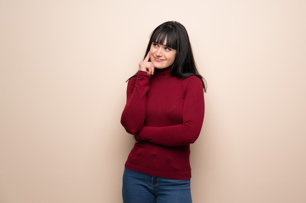 Young woman with red turtleneck thinking an idea while looking up Premium Photo